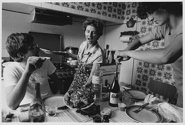 Woman serves lunch to her two adult children in her rural kitchen.