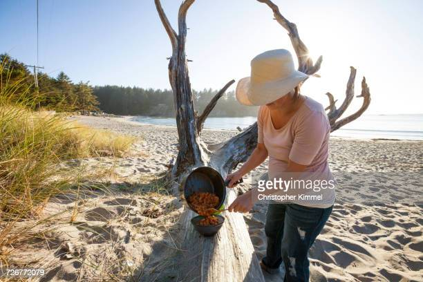 a woman serves pasta dinner while camping on the beach - sunset bay state park stock pictures, royalty-free photos & images
