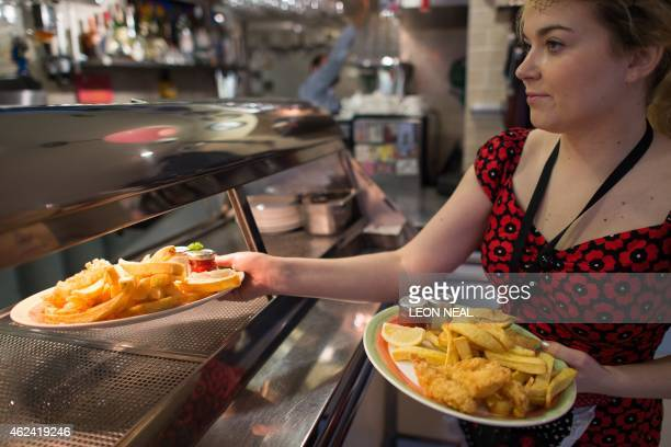 A woman serves plates of fish and chips at Poppies fish and chip restaurant in east London on January 26 2015 Fish and chips that a classic British...