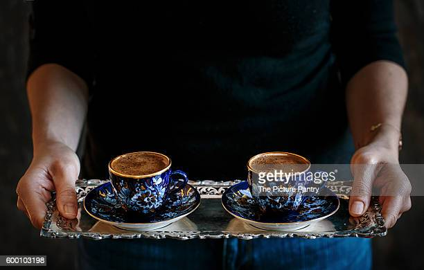 A woman serving 2 cups of Turkish coffee displayed on a silver tray.