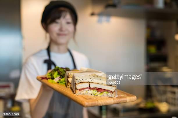 カフェで作りたてのサンドイッチを提供する女性 - 30代の女性 ストックフォトと画像