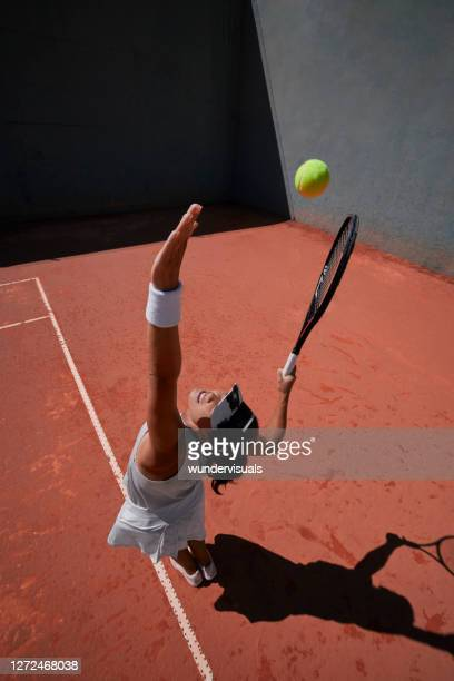 woman serving ball during tennis match on clay court - tennis tournament stock pictures, royalty-free photos & images