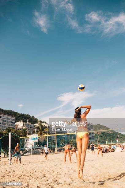 woman serving beach volleyball at copacabana beach in rio de janeiro - beach volleyball stock pictures, royalty-free photos & images