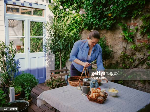 woman serving breakfast outdoor in garden. - guido mieth stock pictures, royalty-free photos & images