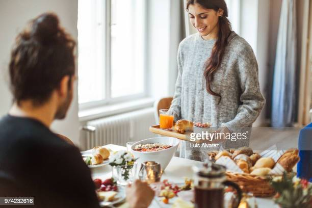 woman serving breakfast to boyfriend at table - breakfast stock pictures, royalty-free photos & images