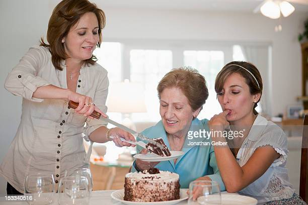 A woman serving cake for her mother and daughter