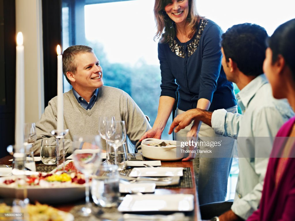 woman serving casserole to friends and family : Stock Photo