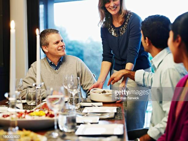 woman serving casserole to friends and family