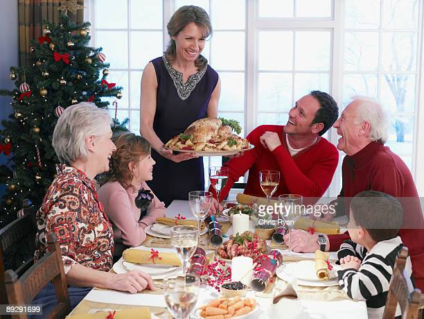 woman serving christmas turkey to multi-generation family at table - british granny stock photos and pictures