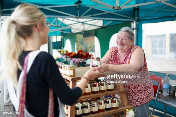 woman serving customer on local market stall. - markt stockfoto's en -beelden