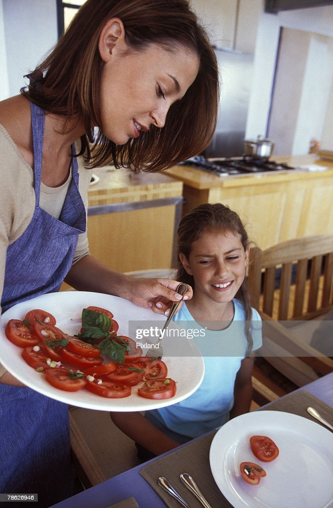 Woman serving daughter meal : Stock Photo