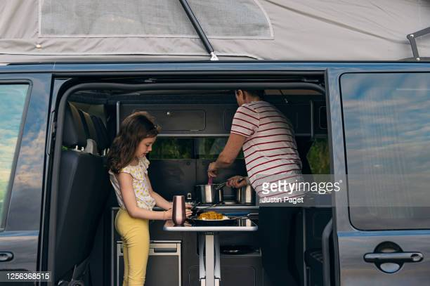 woman serving dinner in her campervan - copy space stock pictures, royalty-free photos & images