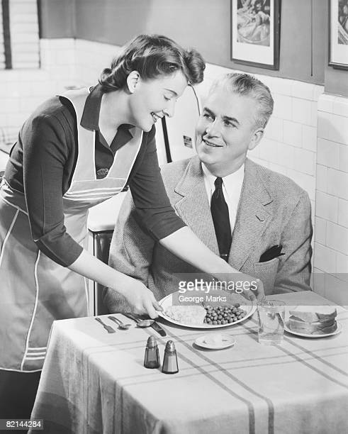 Woman serving dinner to husband, (B&W)