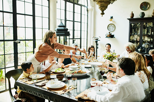 Woman serving family members at dining room table during celebration meal - gettyimageskorea
