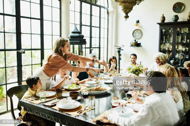 woman serving family members at dining room table during celebration meal - evening meal stock pictures, royalty-free photos & images