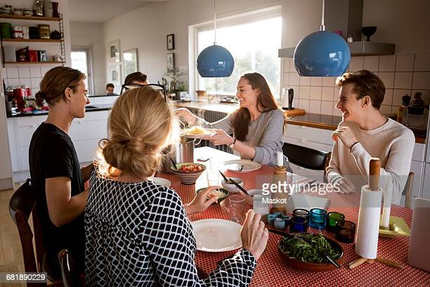 Woman serving food for family at dining table