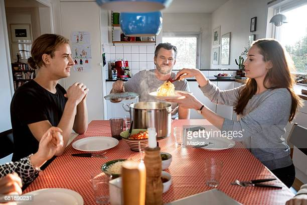 Woman serving food in plate while sitting with family at dining table