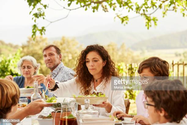 woman serving food to children at table in yard - lunch imagens e fotografias de stock