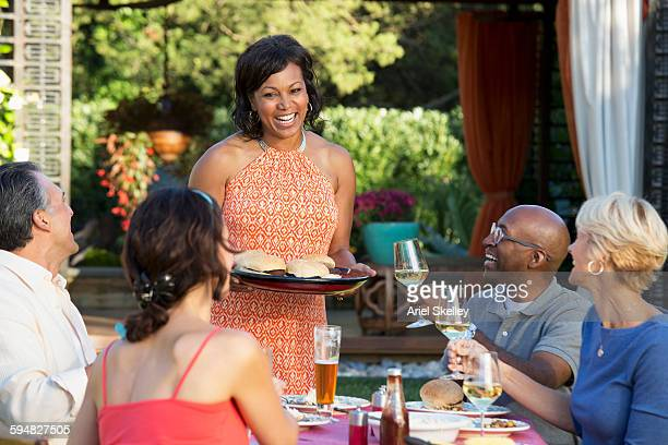 woman serving friends at backyard barbecue - party host stock pictures, royalty-free photos & images