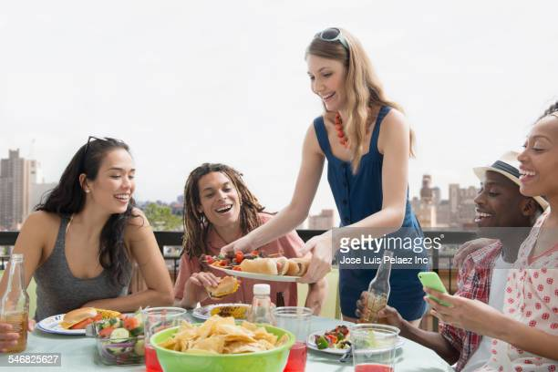 Woman serving friends at barbecue outdoors