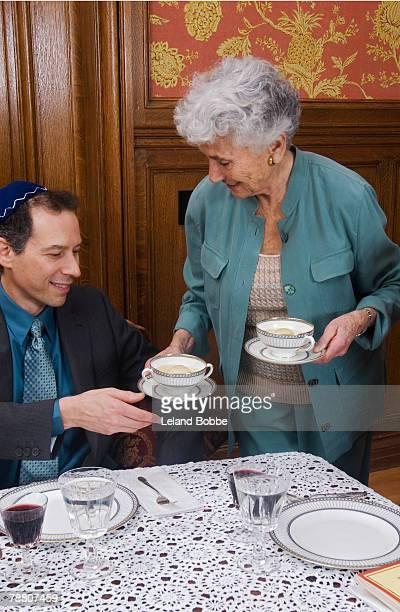 woman serving matzo ball soup - matzah stock pictures, royalty-free photos & images