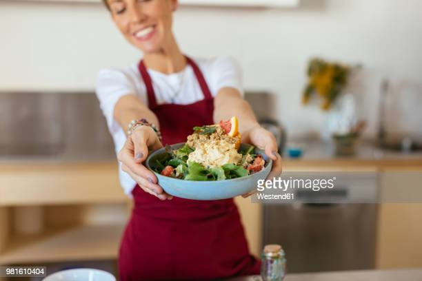 Woman serving meal in kitchen