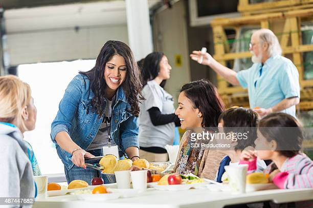 Woman serving meal to young Hispanic family in food bank