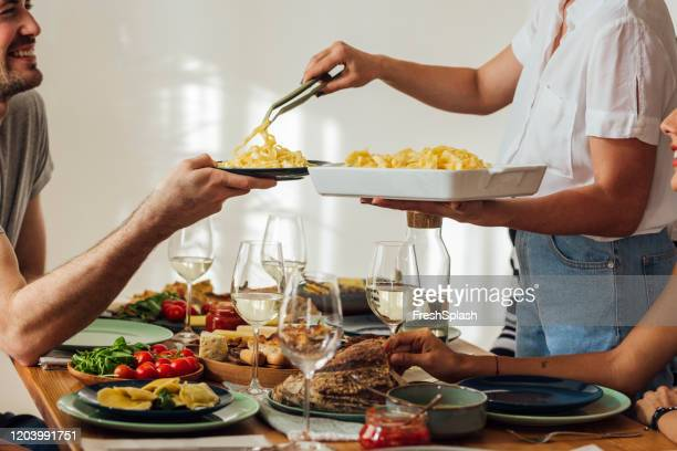 a woman serving pasta at home - spaghetti stock pictures, royalty-free photos & images