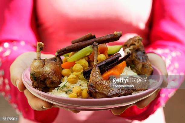 Woman serving roast pigeon with vegetables on noodles (Morocco)