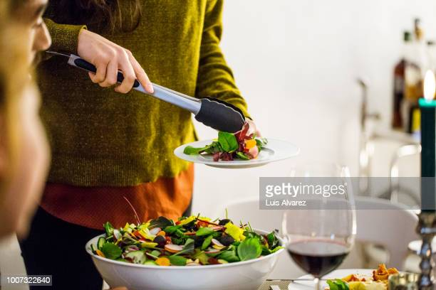 woman serving salad while standing during party - green salad stock pictures, royalty-free photos & images