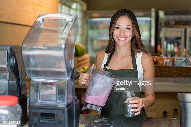 Woman serving smoothies at a small business