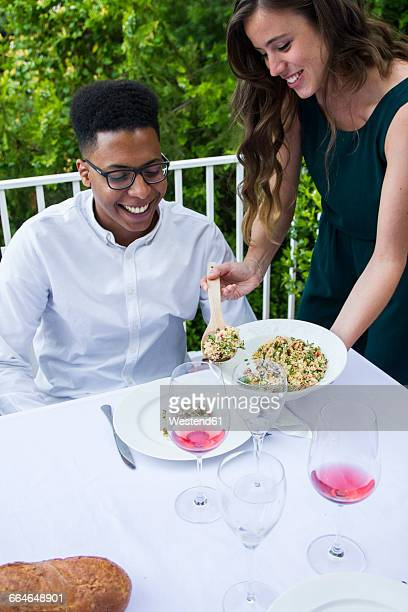woman serving tabbouleh to her guest during a summer dinner - bulgur wheat stock pictures, royalty-free photos & images