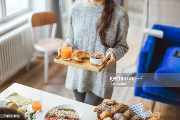 Woman serving tray of healthy breakfast at home