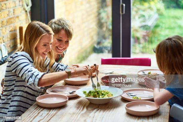 woman serving vegetarian lunch at dining table - lgbtq  and female domestic life fotografías e imágenes de stock