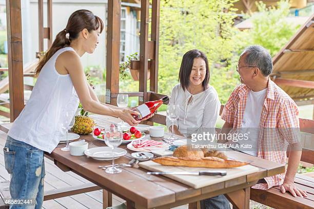 Woman serving wine to parents at dining table