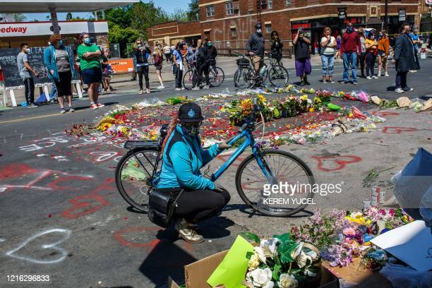 A woman set flowers by a makeshift memorial in honor of George Floyd who died while in custody of the Minneapolis police following a day of...