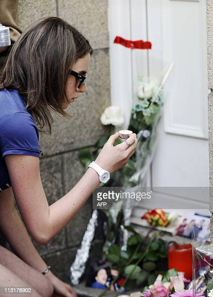 A woman sets a candle in front of the house where the five Dupont de Ligonnes family members were murdered and discovered on April 21 on April 26...
