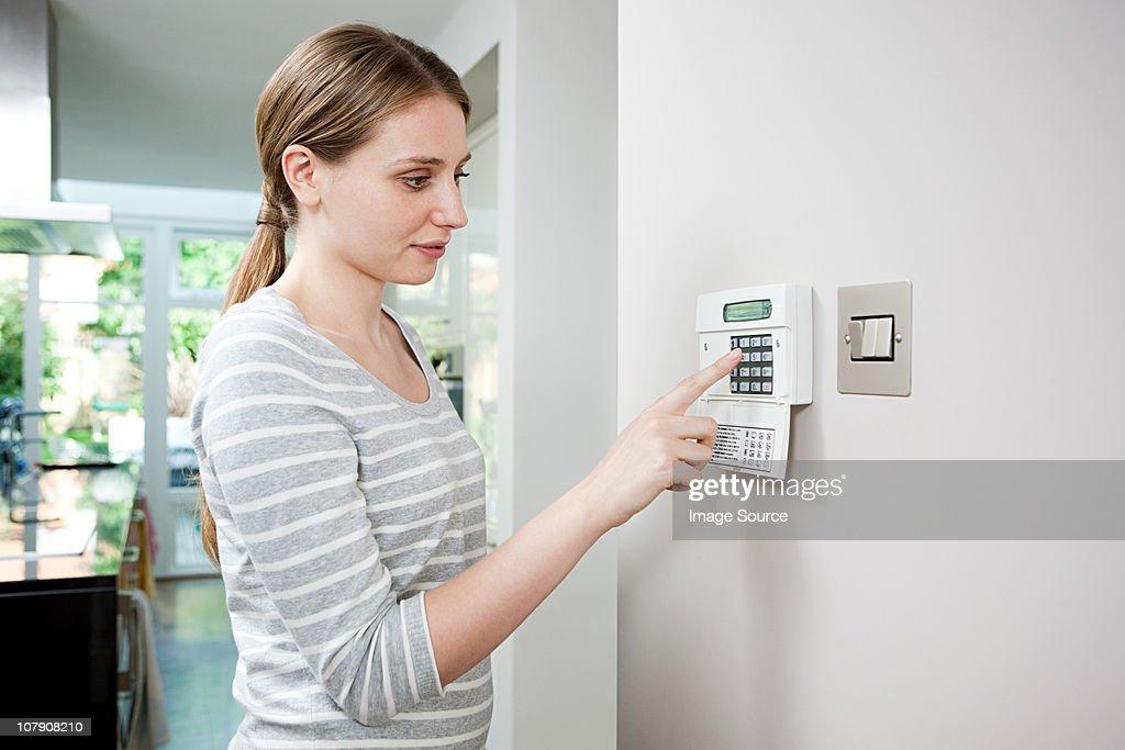 Woman setting burglar alarm : Stock Photo
