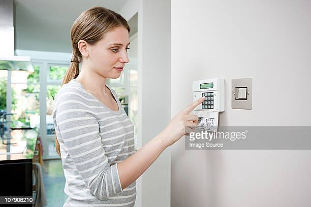 Woman setting burglar alarm