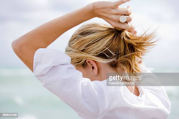 Woman setting hair in ponytail