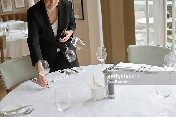 Woman setting out wine glasses in restaurant