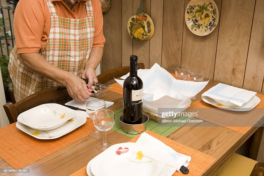 Woman setting table, mid section : Foto stock