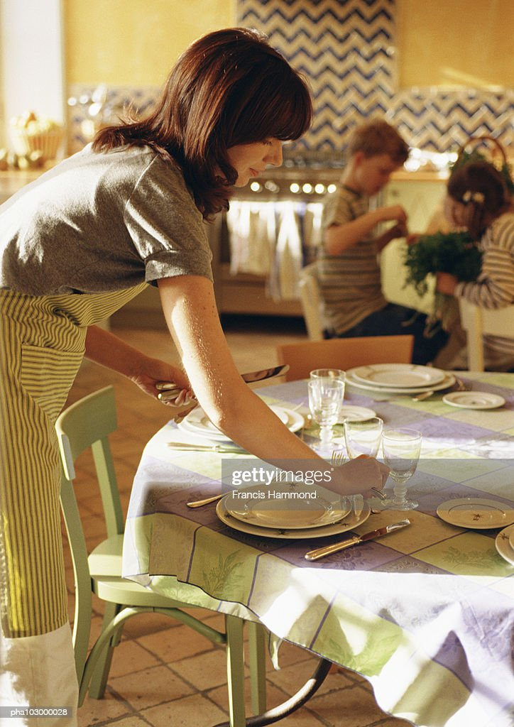 Woman setting the table, side view : ストックフォト