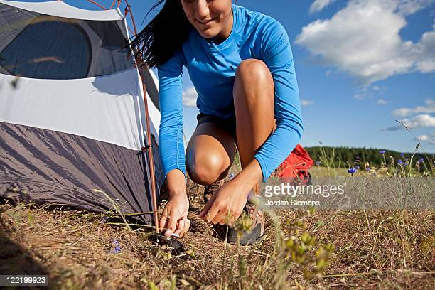 A woman setting up camp.