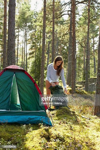 Woman setting up campsite in forest