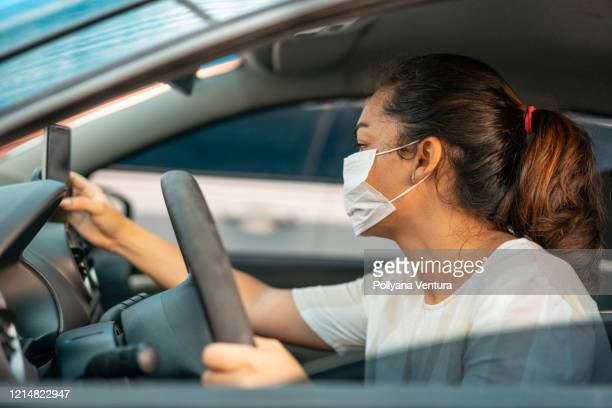 woman setting up gps for car trip - driving mask stock pictures, royalty-free photos & images