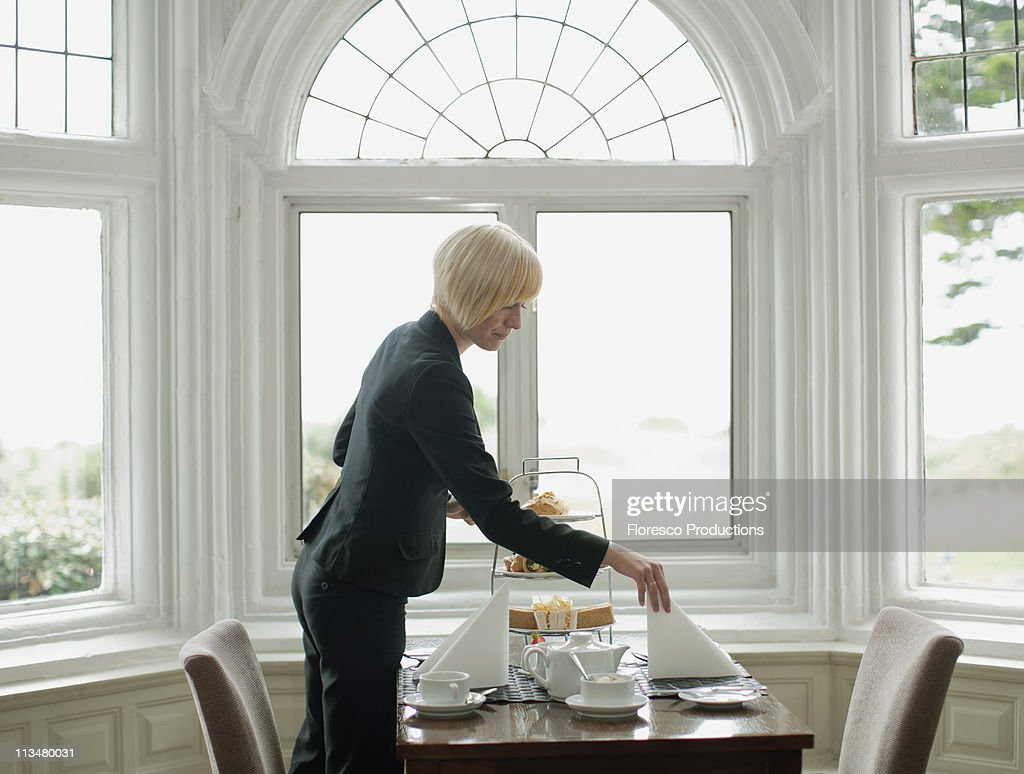 Woman setting up table : Stock Photo