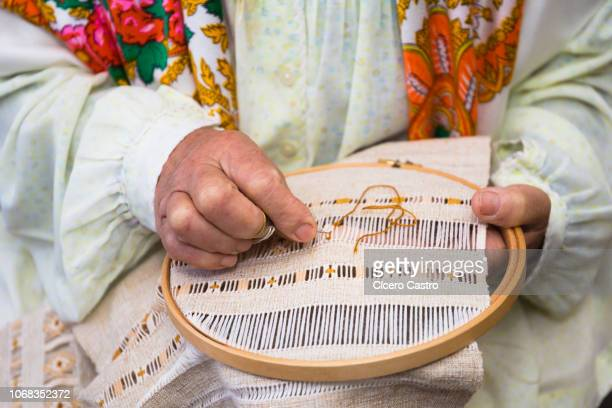 a woman sewing a typical piece of madeira island embroidery. - lareira stock pictures, royalty-free photos & images