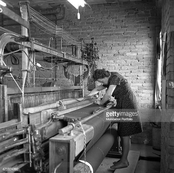 Woman sewing a wool fabric on the loom at home. Biella, 1960s