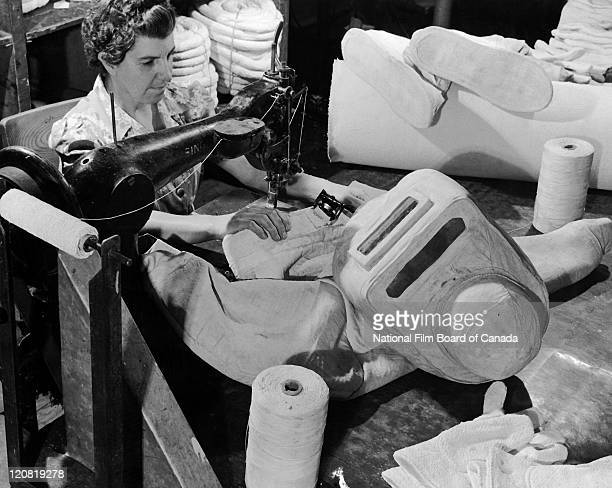 Woman sewing an asbestos fireresistant suit Thetford Mines Quebec Canada 1958 Photo taken during the National Film Board of Canada's production of...